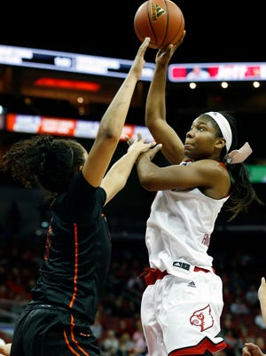Louisville's Myisha Hines-Allen, right, floats a shot over Virginia Tech's Hannah Young.