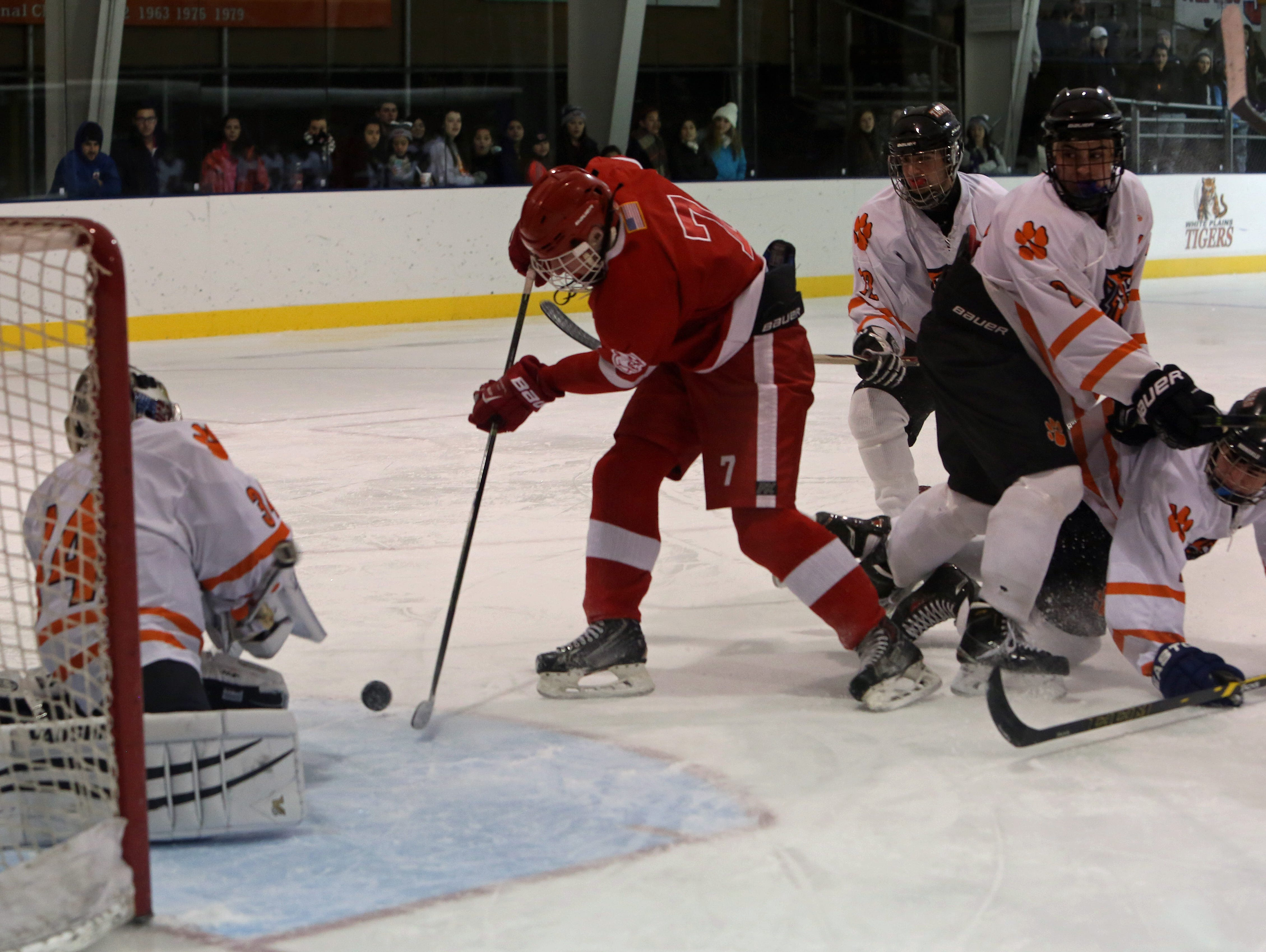 From left, White Plains' goalie Justin Schulz (34) stops a shot from North Rockland's Bryan Jensen (7) during hockey action at Ebersole Ice Rink in White Plains Jan. 7, 2016. The game ended in a 4-4 tie.