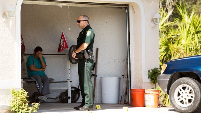 A member of the Lee County Sheriff's Office stands at the scene of a shooting between a home owner and suspects from a suspicious vehicle on Gaylord Ave. in Lehigh Acres. One person who lives at the home was injured in the shooting. The investigation is ongoing. According to the Sheriff's Office the woman to the left is a witness.
