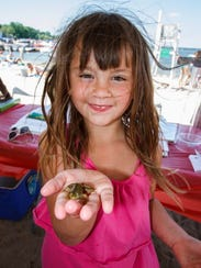 Six-year-old Bella Beltran of Pewaukee holds up a frog