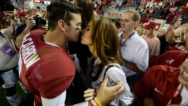 AJ McCarron kisses then-girlfriend Katherine Webb following the Crimson Tide's win against Arkansas in October of 2013.