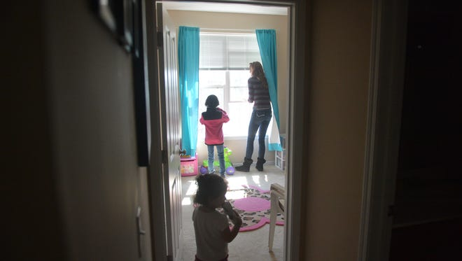 """Rachel Cook opens windows with the help of her boyfriend's daughter, Malaya Waddy, 9. Cook's daughter, Jaela Washington, 2, stands in the doorway of her bedroom at Waterford Village. """"It's a nice environment,"""" Cook said. """"Clean and a lot more space. There's a lot of kids around a lot of single parents like me."""""""