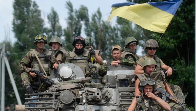 Ukrainian government soldiers sit atop an armored personal carrier with a Ukrainian national flag, outside the city of Siversk, Donetsk region, eastern Ukraine on July 12. Pro-Russian insurgents last week retreated from the strategic city of Slovyansk and holed up in Donetsk, a city of one million, and potentially the final frontier for the rebels.