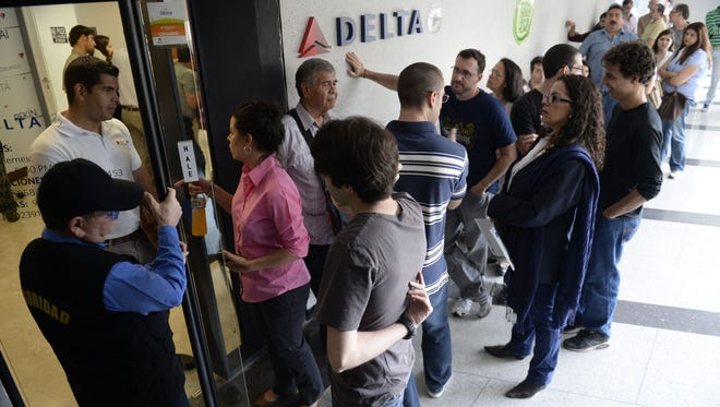 People queue outside the Delta sales office in Caracas, on July 7, 2014. Delta Air Lines announced Monday it is cutting its flights to Venezuela to one a week amid a currency dispute with Venezuela.