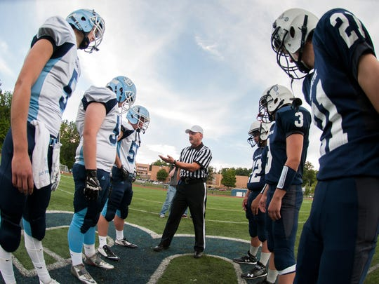 Team captains stand at midfield for the coin toss before the start of the football game between the South Burlington Rebels and the Burlington Seahorses at Buck Hard Field on a Friday night in 2014.