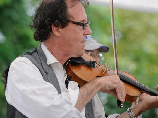 Michael Francis, of Oak Park, plays the fiddle during 2013 Thumbfest. Many musicians come to jam with others throughout Lexington.
