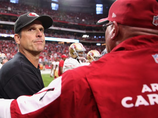 Jim Harbaugh of the San Francisco 49ers shakes hands with head coach Bruce Arians of the Cardinals following the NFL game at the University of Phoenix Stadium.
