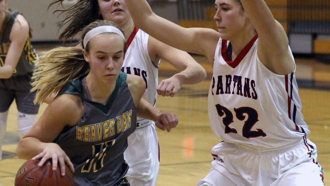 Beaver Dam's Paige Schumann drives past Brookfield's Nikki Pink (left) and Molly DeValkenaere on the way to the basket.  Schumann finished with 13 points.