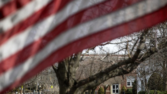 An American flag flies outside Saint Raphael Academy in Pawtucket, R.I., which is closed March 2 after two people who returned from a school trip to Europe tested positive for the new coronavirus disease, health officials said.