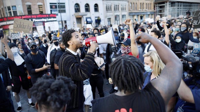 """Leading the crowd in a chant of """"We have a voice,"""" Ohio State basketball player Seth Towns used a bullhorn and said, """"Everybody who I love has texted me and said 'Stay out of harm's way,' ... but I'm always in harms way."""""""