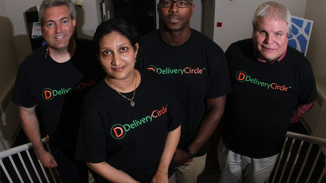 DeliveryCircle CEO and founder Vijaya Rao (front) and other team members stand together at the Emerging Enterprise Center in New Castle in 2015.