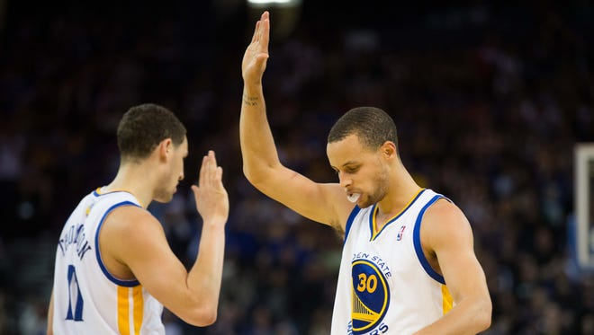 Golden State Warriors guard Stephen Curry (30) high fives guard Klay Thompson (11) after the basket and one against the Milwaukee Bucks during the fourth quarter at Oracle Arena. The Golden State Warriors defeated the Milwaukee Bucks 115-110.