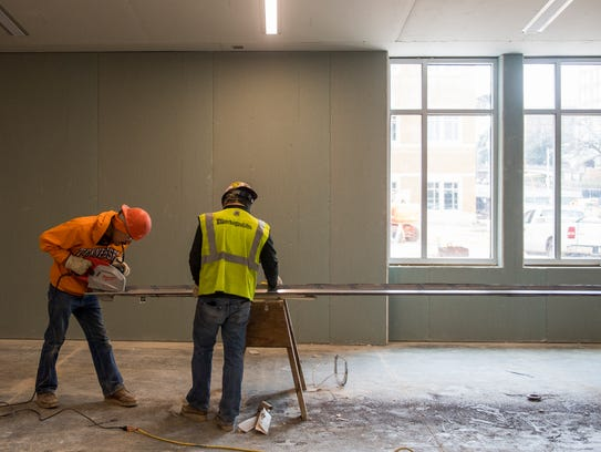 Construction workers work in the main hallway of the