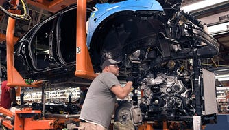 A worker places engines into Cadillac XT5 and GMC Acadia vehicles Wednesday, Feb. 14, 2018, at the General Motors plant in Spring Hill.