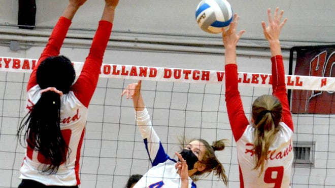 Saugauck's Aerin Baker (center) slams a kill against Holland earlier this season.