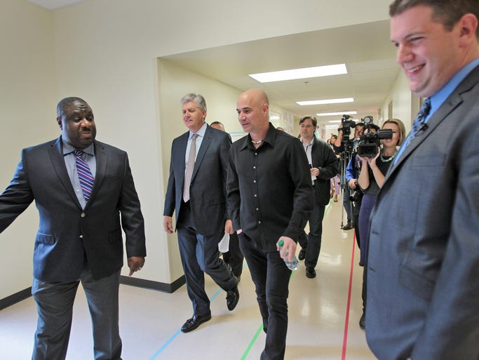 Tindley Accelerated Schools chancellor Marcus Robins, from left, Glenn Pierce, tennis star Andre Agassi, and Tindley Renaissance Academy principal Todd Hawks are joined by others touring, Tindley Renaissance Academy, Thursday, April 24, 2014.