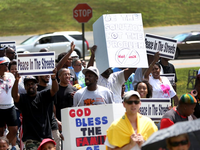 Marchers carry signs and chant slogans during the Peace in the Street Parade Walk in Indianapolis on Sunday, July 13, 2014. The UniverSoul Circus and the City of Indianapolis teamed up for the parade beginning at the Brightwood Community Center and ending at Washington Park.