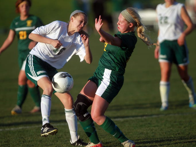 West High's Claire McDonnell, left, collides into Cedar Rapids Kennedy's Jessica Wagner during their game on Friday, May 9, 2014. David Scrivner / Iowa City Press-Citizen