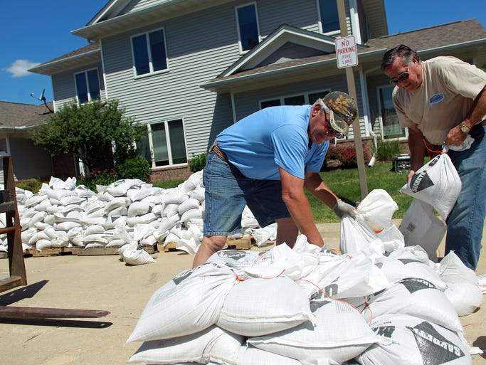 Tracy Hansen, left, and Gene Fisher load sandbags onto a pallet on Pentire Circle off of Idyllwild Drive on Friday, July 4, 2014. David Scrivner / Iowa City Press-Citizen