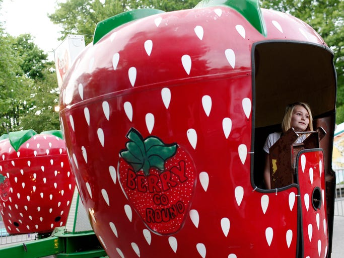 """Alicia Severson, 13, rides the Berry Go Round during """"Ride Night"""" held on the first night of the annual church picnic fundraiser for Saint Elizabeth Ann Seton Catholic Church.  May 8, 2014"""
