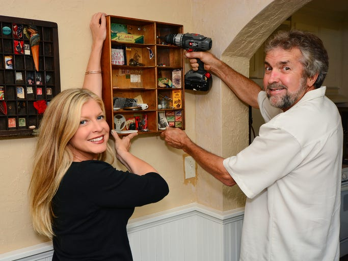 Michael O'Donovan helps Shelley hang antique trays filled with family mementos. For more stories and photos, see the July issue of Pensacola Bella Magazine, and go to www.BellaMagazine.com. <o:p></o:p>