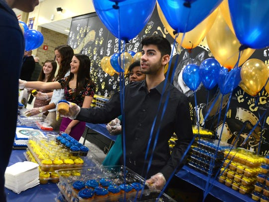 Junior, Arlon Marrogy, helps hand out cupcakes Monday, Jan 26, for the 50th birthday celebration of Port Huron Northern.