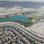 The Coachella branch of the All-American Canal snakes between a housing development and a man-made water-ski lake near the open undeveloped desert in north Indio.