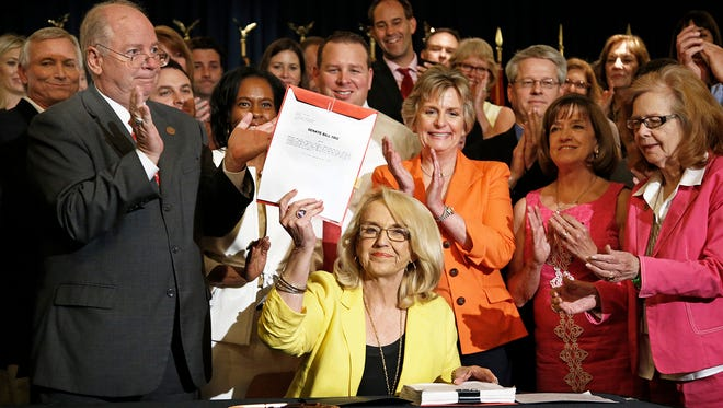 Arizona Gov. Jan Brewer shows off the recently signed Senate Bill 1002 on May 29 2014. The bill provides about $60 million in additional funding to cover the cost of adding more than 160 new staff for the newly created Department of Child Safety.