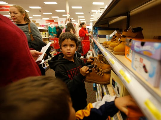 Decklyn McQuerry picks out a pair of boots Wednesday while shopping at Target in Farmington.