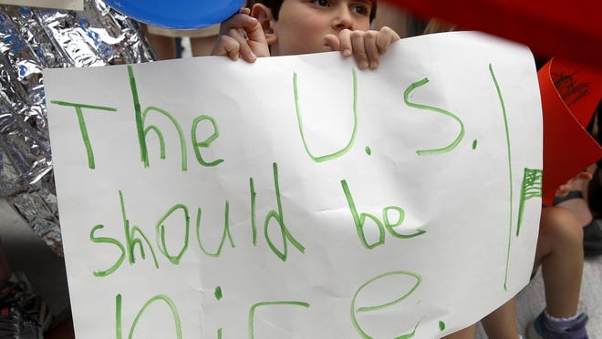 Shua Rich, age 6, holds his sign as he protests with his mother during a rally against U.S. immigration policies outside an office for Rep. Kevin Yoder, Friday, June 22, 2018, in Overland Park, Kan. (AP Photo/Charlie Riedel)