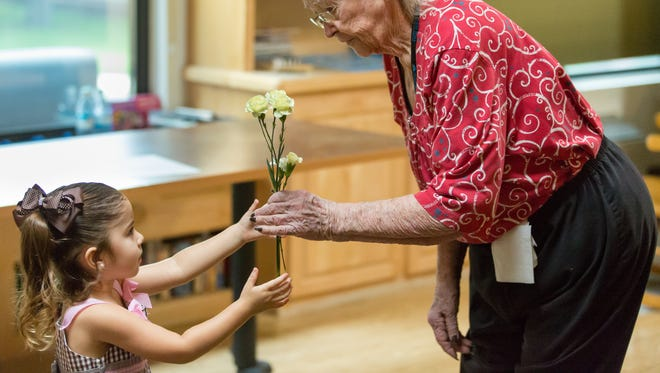 "Desert Peaks Assisted Living & Memory Care resident June Hardin, receives flowers from Ember Chavez, 2, on Friday, August 11, 2017 during ""inter-generational day.""  Bambi Daycare Home students made crafts with the residents as they learned to respect elders."
