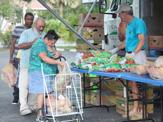 Visitors to the Golden Gate Community Center receive help from the Harry Chapin Mobile Food Pantry.