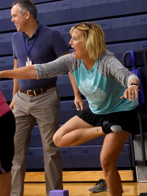 Dallastown Area High School women's tennis coach Deb Gable tries her hand at yoga during the school's annual Wellness Fair. The event included massages, a golf assessment, laser tag and demonstrations on healthy cooking.