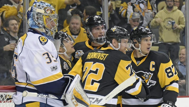 Penguins right wing Patric Hornqvist (72) is congratulated by center Sidney Crosby (87) after scoring a goal on Predators goalie Pekka Rinne (35) in the second period Tuesday.