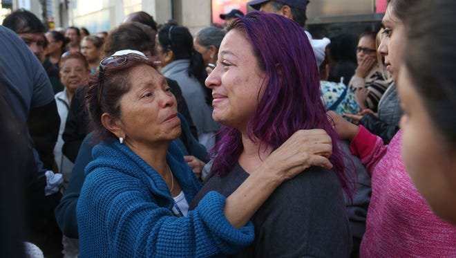 Marta Linares, who said she nearly got on the bus that crashed, left, consoles the daughter of one of the Sunday's fatal bus crash victims Jennifer Ruiz, right, during a candlelight vigil for those killed in Los Angeles, October 24, 2016.