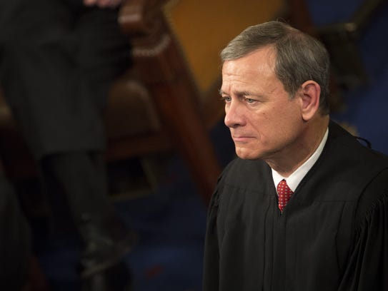 Chief Justice John Roberts listens as President Obama