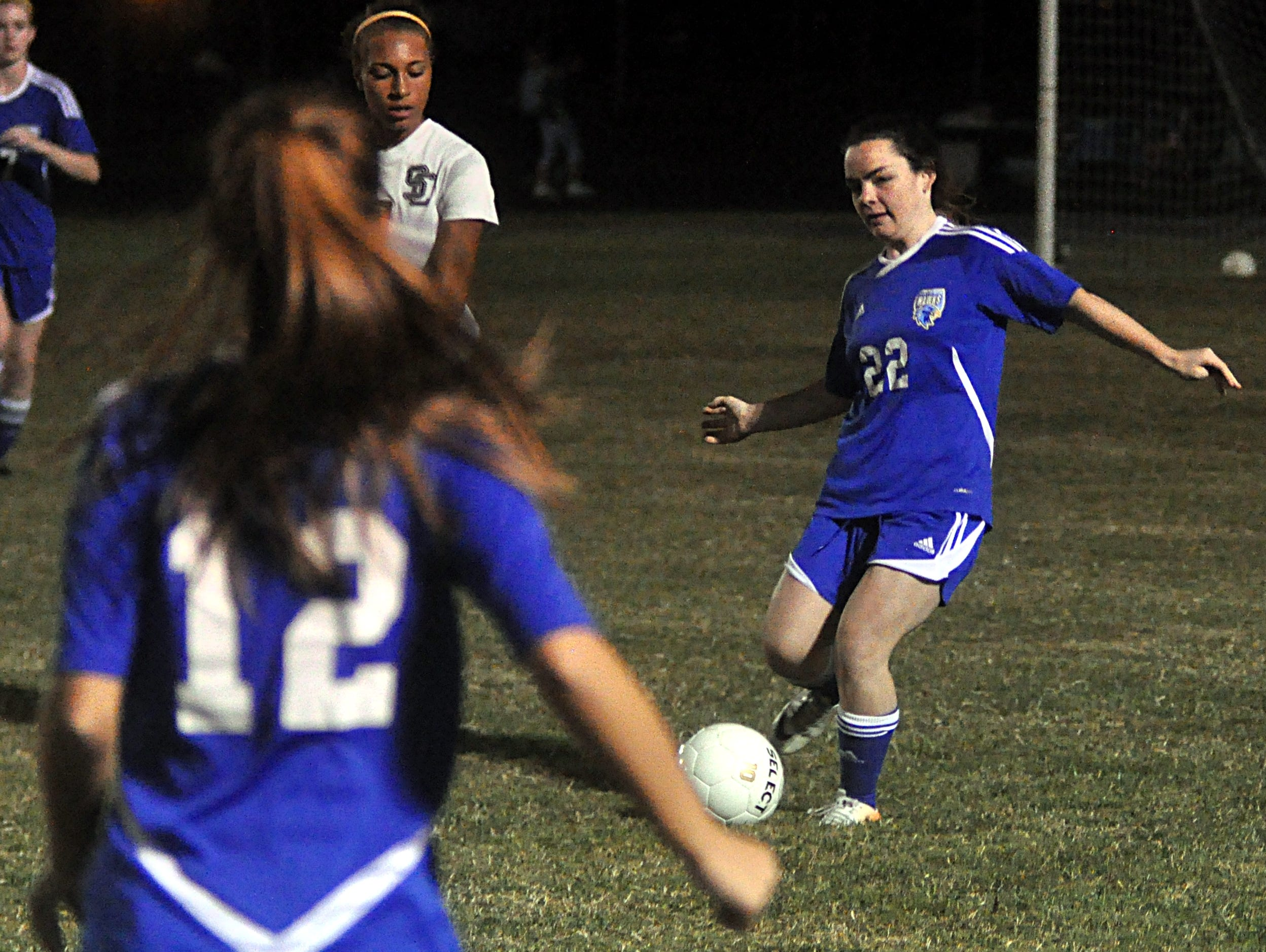Merrol Hyde Magnet sophomore Emily Fenton (22) passes to junior Addison Oaks (12) during first-half action.