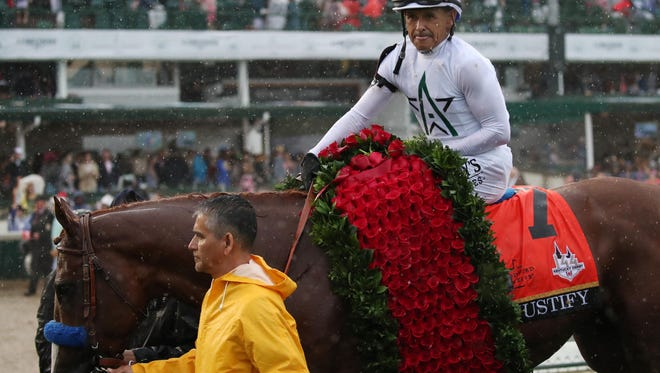 Mike Smith aboard Justify in the winner's circle after winning the 144th running of the Kentucky Derby at Churchill Downs.