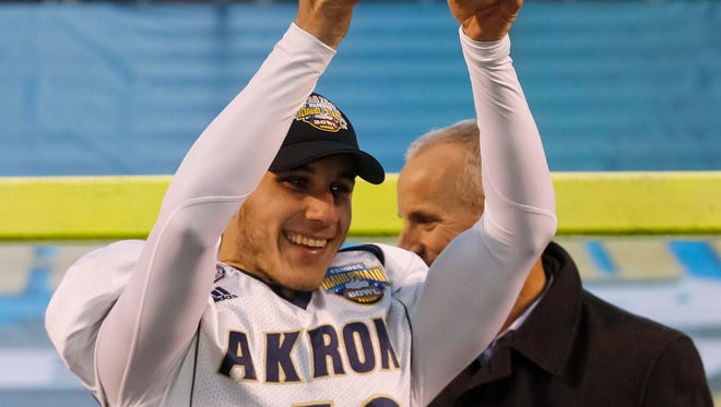 Akron kicker Robert Stein holds up his MVP trophy after Akron's 23-21 win over Utah State in the Famous Idaho Potato Bowl NCAA college football game in Boise, Idaho, on Tuesday, Dec. 22, 2015.