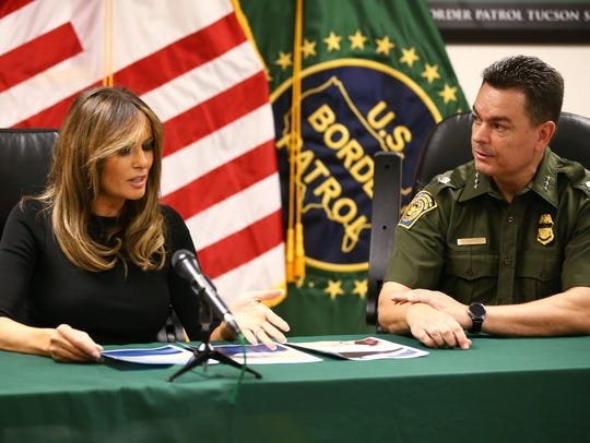 First lady Melania Trump looks at photos of an abandoned