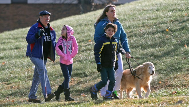 Eight-year-old twins Kelly and Sean Pizzolo walk home from their elementary school  with their parents, Gary Pizzolo, left, and Kris Heist, as well as guide dog Christy Campbell.