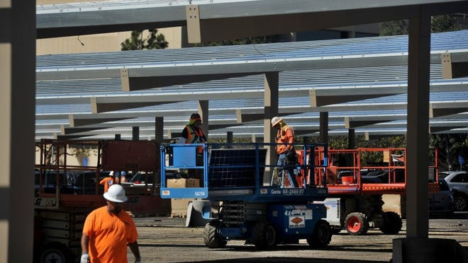 Work crews construct and install a solar panel power system in the parking lot of the Ventura County Government Center