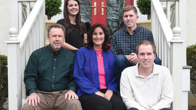 """Michelle Ironside Henry, center, sits on her front porch with, from left, husband David Henry, daughter-in-law Samantha Henry, and sons Drew and Evan Henry, on March 19, 2016. Michele Henry wrote in her book, """"My Anchor Holds,"""" that she relied on faith as she continued her battle against colon cancer."""