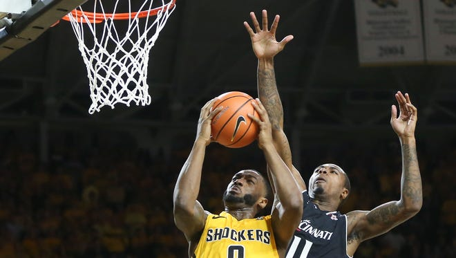 Wichita State forward Rashard Kelly goes to the basket against Cincinnati forward Gary Clark during the first half of the game Sunday, March 4, 2018 in Wichita, Kan.