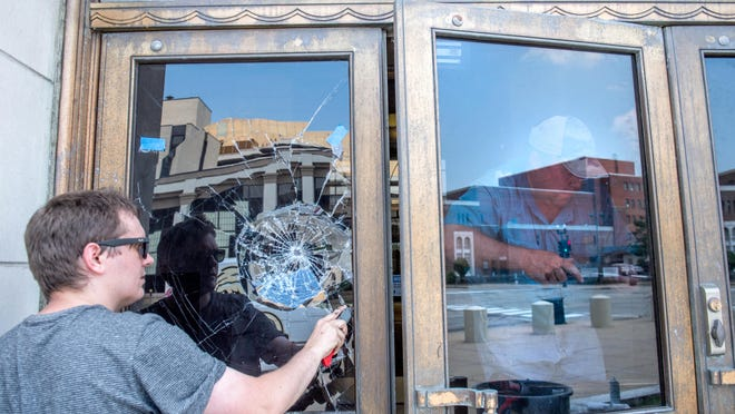 Tyler Dillon, left, of Baer Glass, works at removing a smashed pane of glass while Noel Baer replaces another one Monday, July 6, 2020 at the Federal Building and U.S. Courthouse in Downtown Peoria. Danny G. Jeffery, 38, of Metamora was arrested Sunday for allegedly destroying twelve panes with a rock.