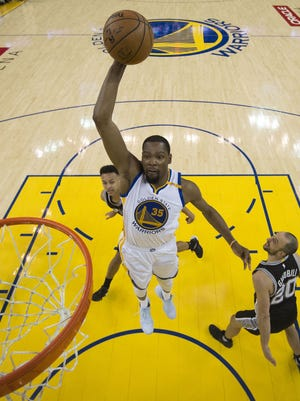Golden State Warriors forward Kevin Durant dunks the basketball against San Antonio Spurs guard Manu Ginobili during the second half in Game 1 of the Western Conference finals.