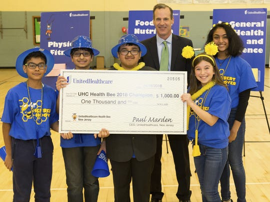 Paul Marden, UnitedHealthcare of New Jersey CEO presents Herbert Hoover with the grand prize at the 2018 UnitedHealthcare Health Bee competition in Metuchen.