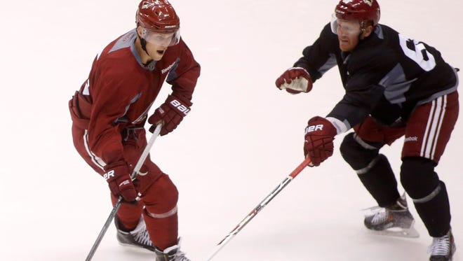 Henrik Samuelsson, left, battles James Melindy, right, for the puck during the Arizona Coyotes' rookie camp on Saturday, Sept. 13, 2014, at Gila River Arena in Glendale, Ariz.