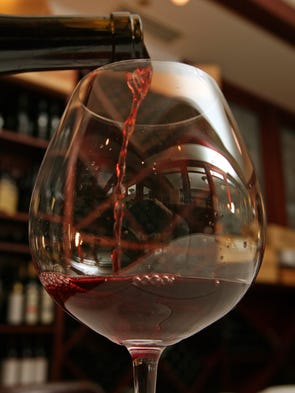A sommelier at 801 Chophouse in Des Moines pours a glass of wine.