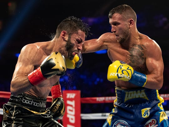 Vasiliy Lomachenko, right, battles Jorge Linares in their championship bout.